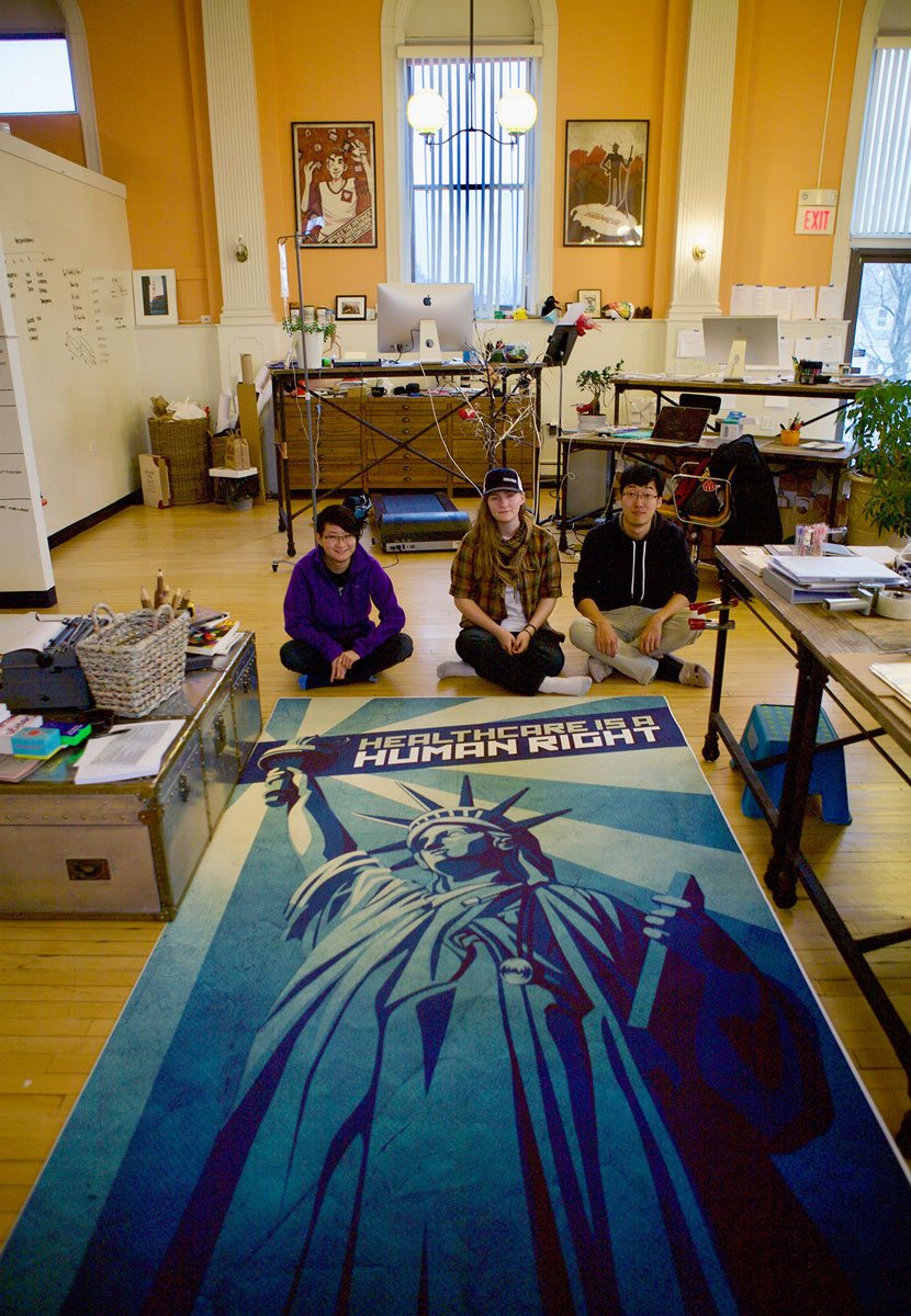 Invo team members having fun displaying their 'Healthcare is a Human Right' large-scale print-out on the floor