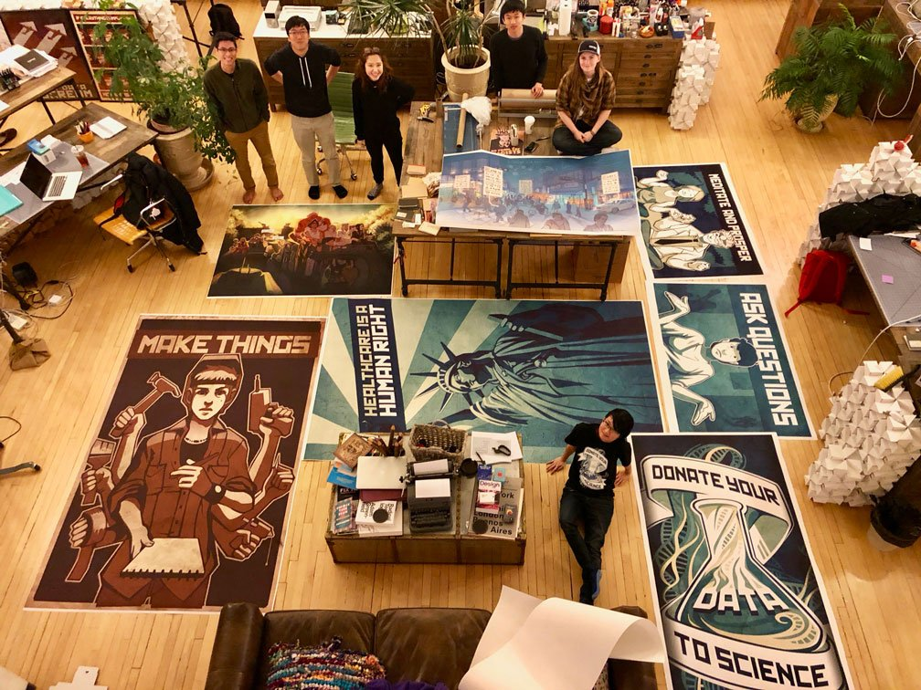 Overhead shot of Invo artwork printed very large, spread out on the floor with the studio team scattered around smiling